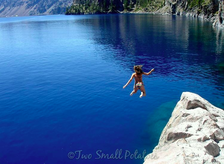 Girl jumping off cliff into Crater Lake