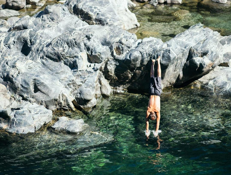 Person diving off rock boulder into water
