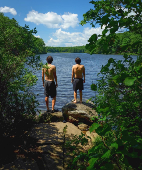 Two boys standing on rocks looking out across Benedict Pond