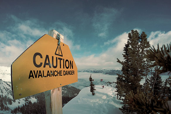 Caution Avalanche Danger sign on top of snow covered mountain peak
