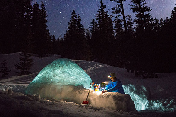 Man with headlamp on building igloo shelter deep in snow