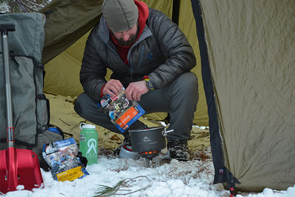Mountain House Ambassador Clint Stout preparing Mountain House entree in tent during winter