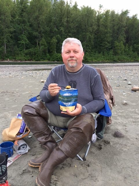 man sitting in chair on bank eating mountain house while on fishing trip