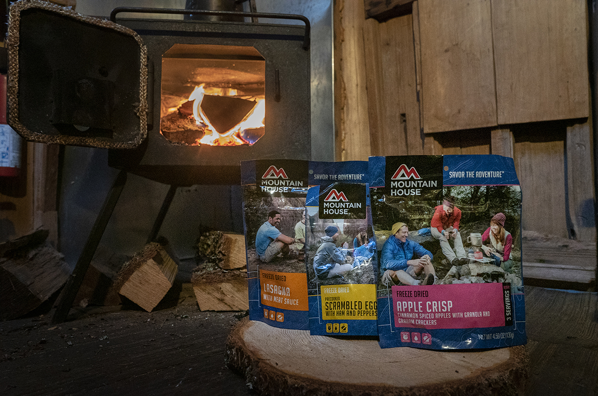 a woodstove with 3 MountainHouse pouches in the foreground