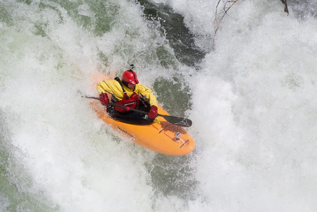 Kayaker in cold weather gear going through a rapid