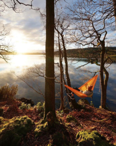 person in orange hammock staring across water