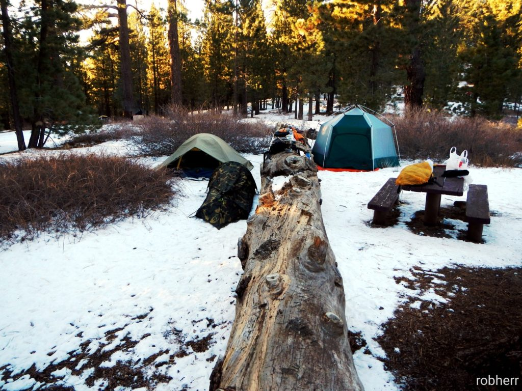 winter campground with two tents, a picnic table, and snow on the ground