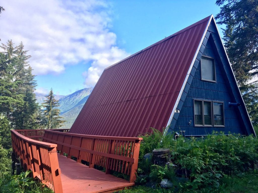 Blue A-frame with red roof and blue sky background