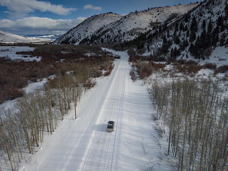 Drone shot of a camper van on a snowy road with trees on either side