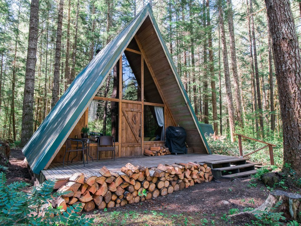 Wooden A-frame cabin surrounded by tall trees with a stack of wood out front.