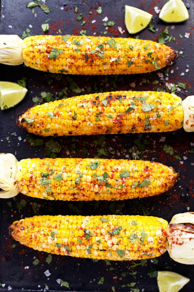 corn on the cob with lime wedges, crushed pepper, and cilantro