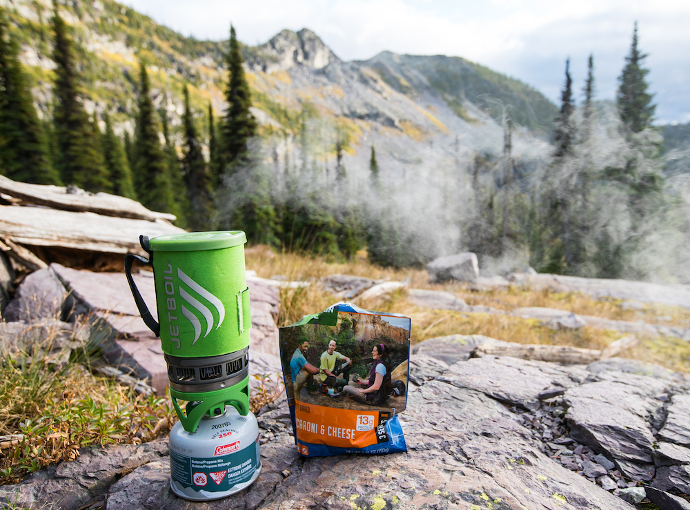a steaming JetBoil and Mountain House pouch of macaroni and cheese with a background of Glacier National Park