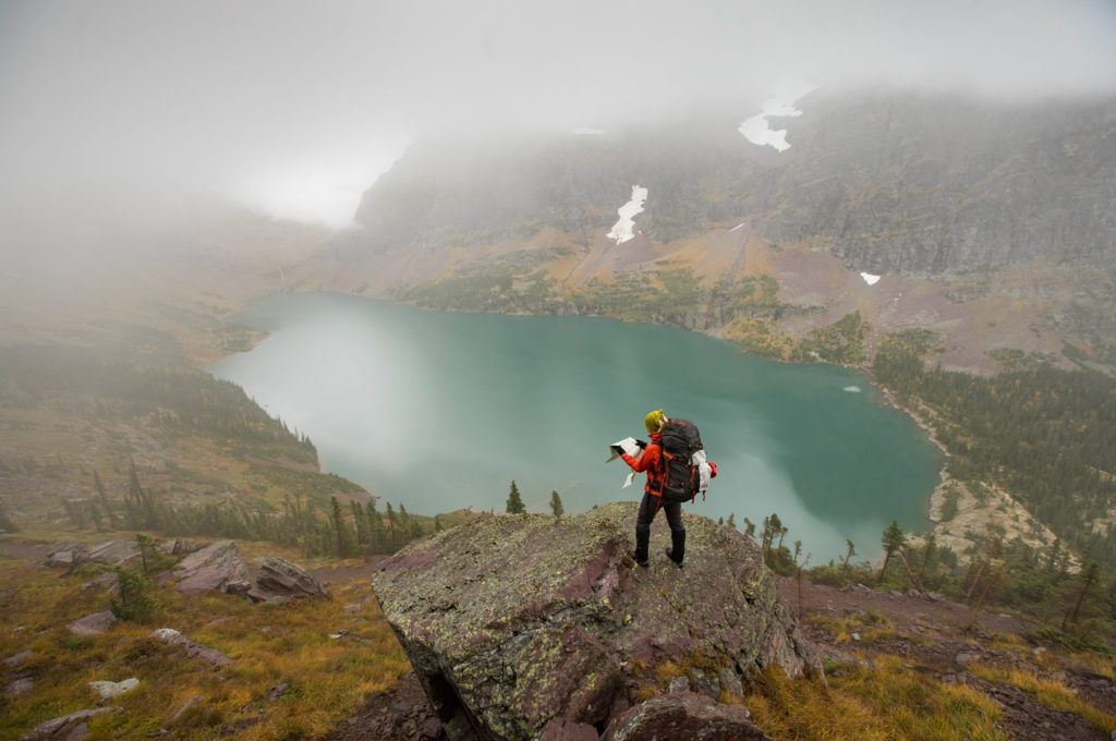 person standing above a lake at Glacier National Park holding a map and wearing a modern internal frame backpack