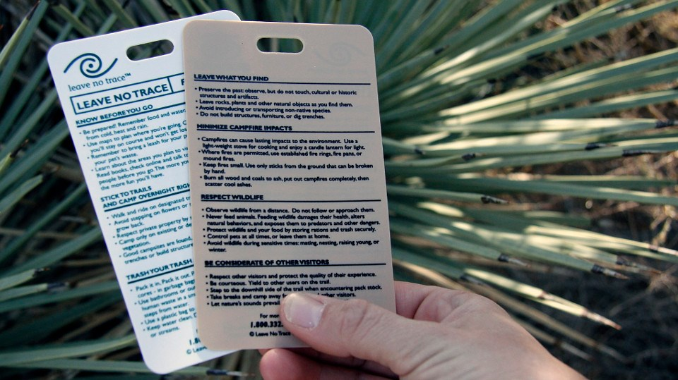 a person's hand holding two cards with the principles of Leave No Trace.