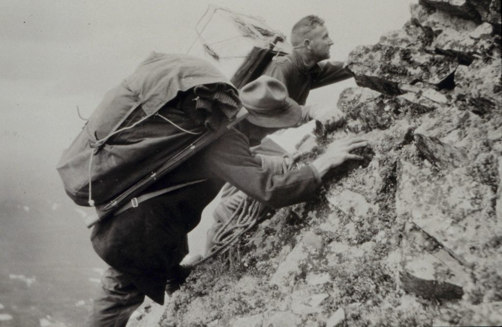 A black and white photo from 1923 of two people scrambling up a rocky hillside with large packs on their backs.