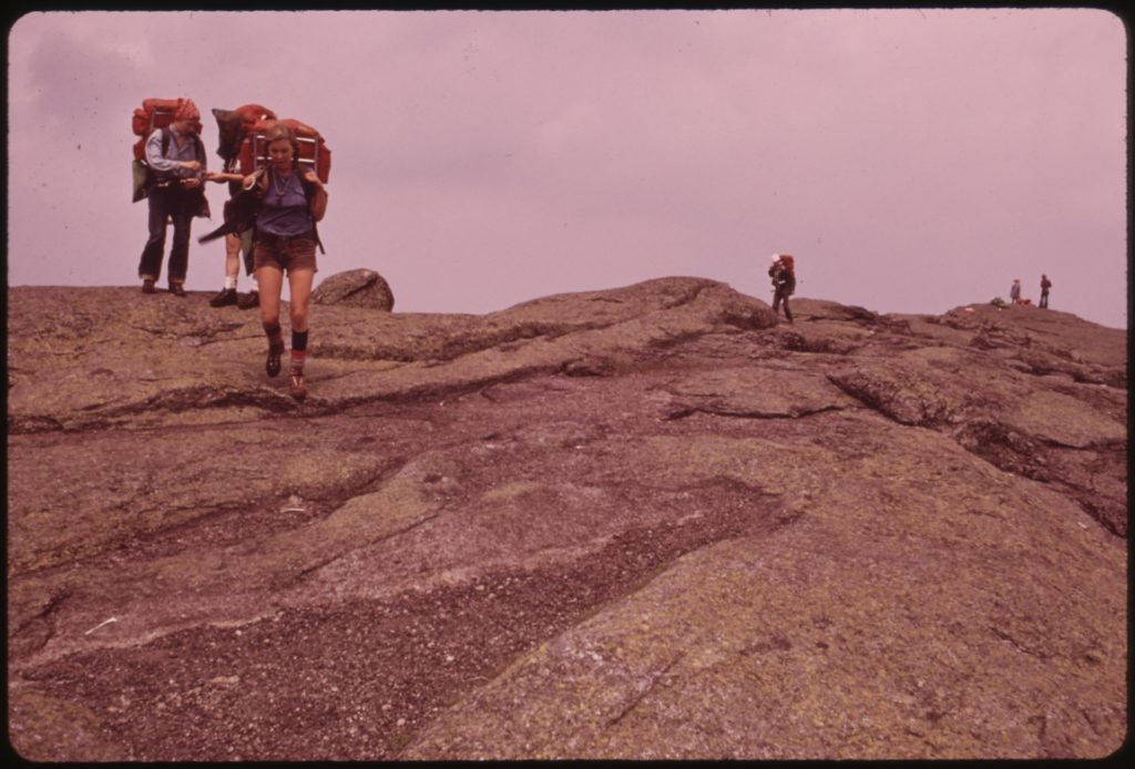 a sepia-toned photo of people backpacking over a boulder field with large exterior frame backpacks