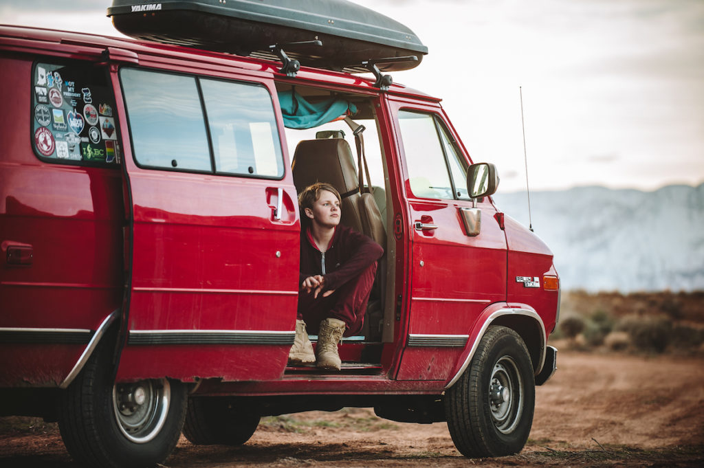A red van with the door open and a teen sitting in the doorway gazing into the distance.