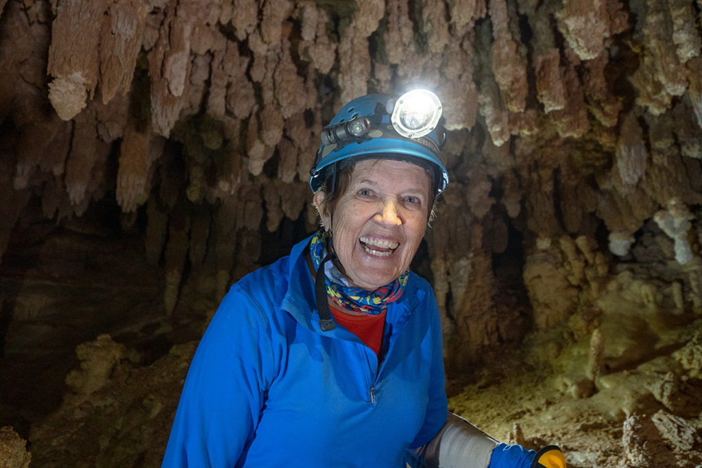 Phyllis is wearing blue and has a blue helmet on with a bright headlamp. She is smiling and is standing under stalagtites. Photo credit John Waller/Uncage the Soul Productions