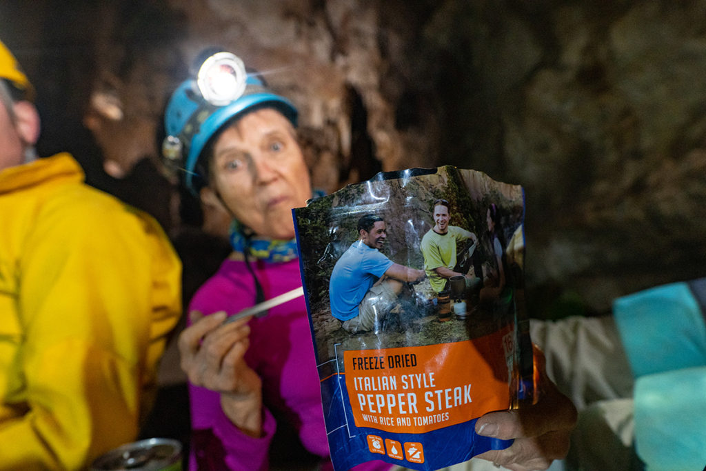 "Phyllis is in a blue helmet with a bright headlamp and is holding a metal spork in her hand with a pouch of Mountain House freeze-dried food in front of her. Her facial expressions looks like ""Wow! That's amazing!"" Photo credit John Waller/ Uncage the Soul Productions"