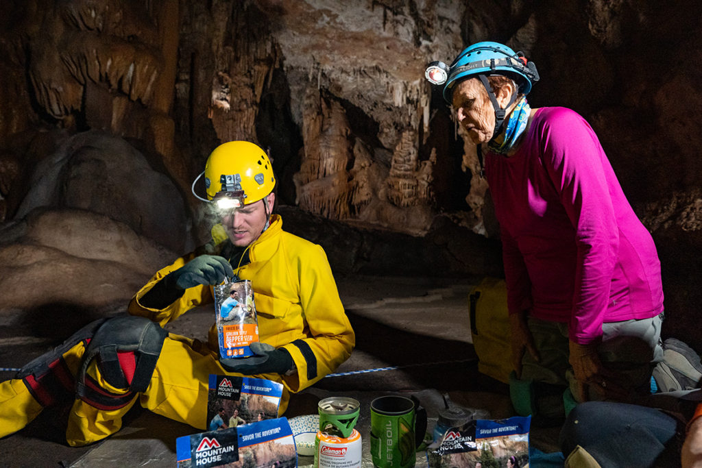"Caver Liam is in yellow and is opening up a pouch of Mountain House freeze-dried food, while Phyllis in pink looks on with a look of ""ooh"" on her face. Photo credit John Waller/Uncage the Soul Productions"