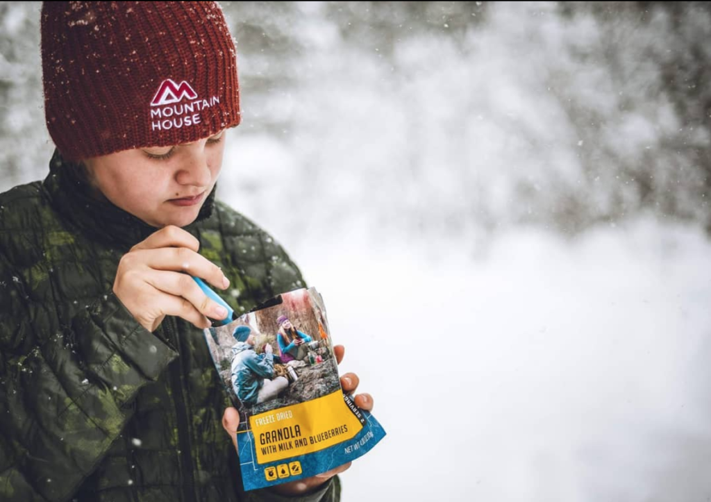 A teen in a Mountain House beanie eating from a pouch of Granola with Blueberries.