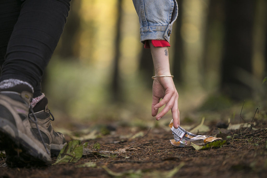 A person's hand picking up a wrapper from a trail.