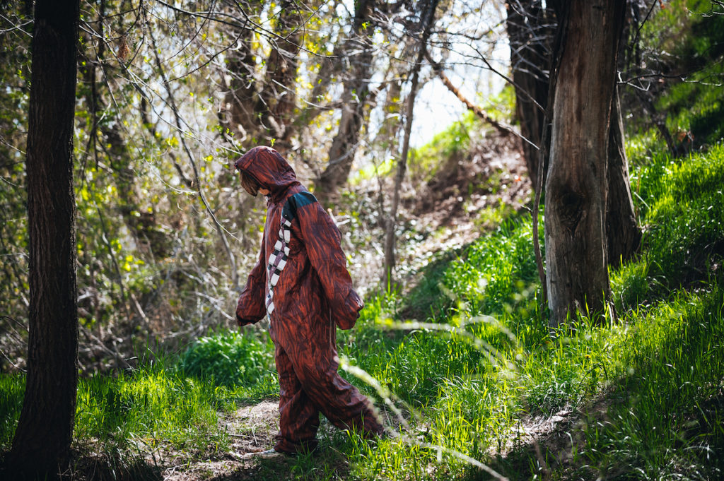 Someone wearing a Chewbacca Star Wars onesie while walking through the woods.