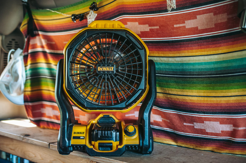 A black and yellow DeWalt fan against a colorful blanket inside a van.