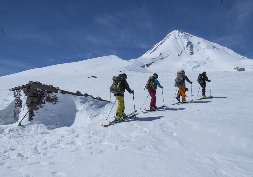 Four skiers ascend a snowy mountain beneath blue skies.