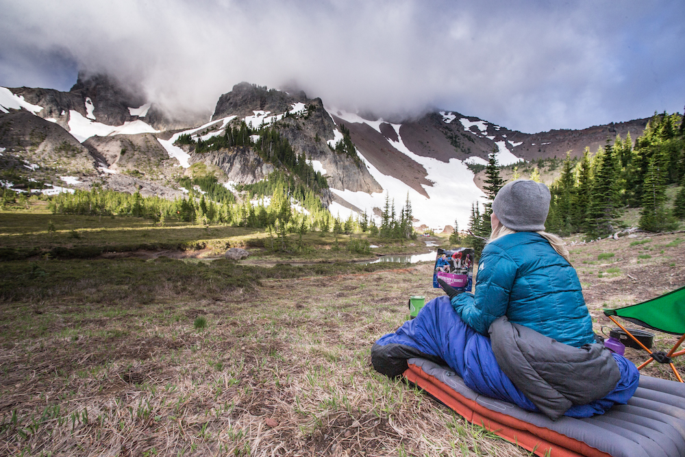 A person enjoys spring backcountry camping on a sleeping pad while staring at the snowy side of a mountain while holding a pouch of Mountain House.