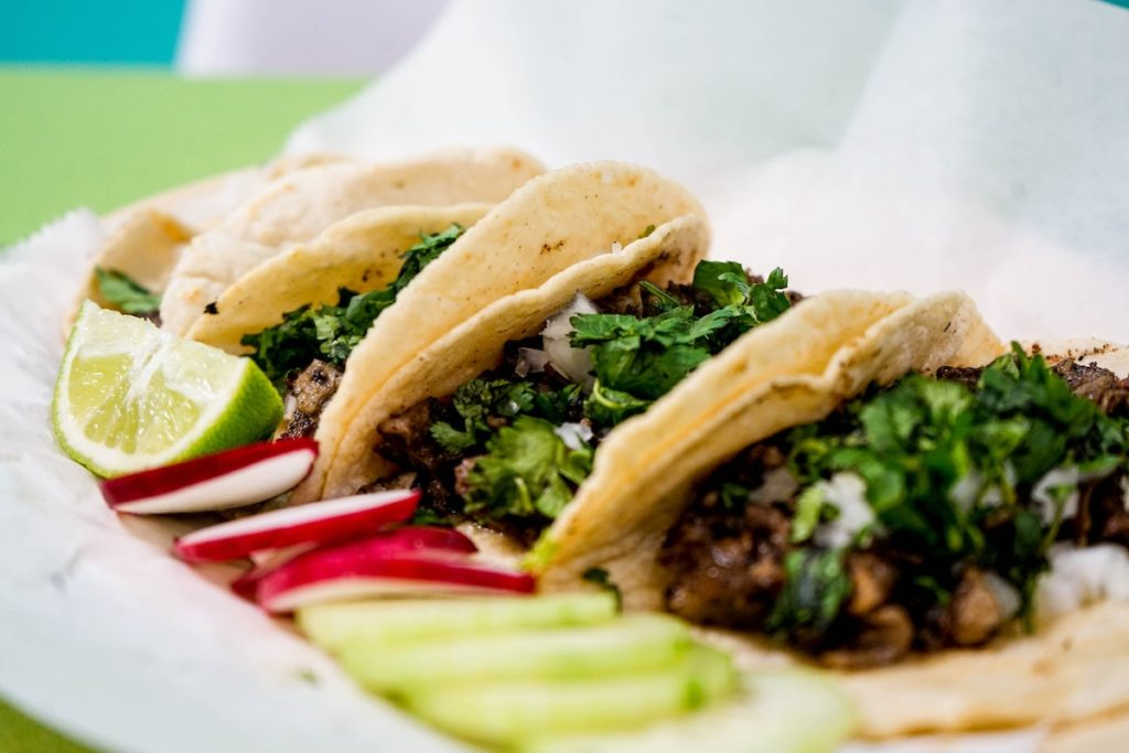 four tacos with lime and radishes