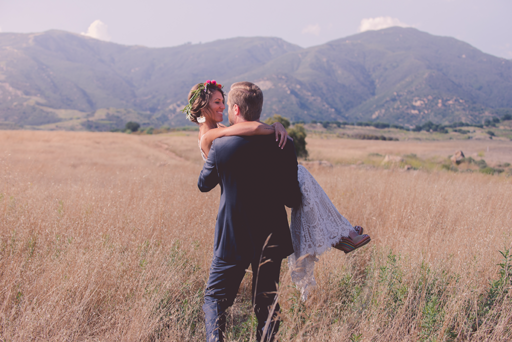 A groom carries a bride through a tall field of yellow grass.