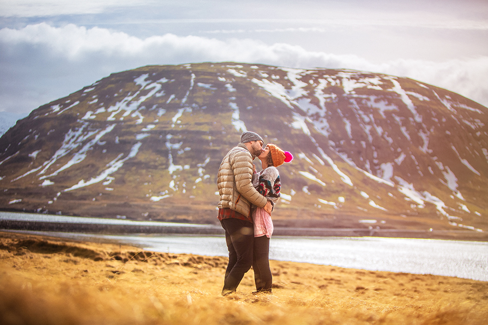 A newly engaged couple kisses in a yellow field with a snow dusted mountain behind them.