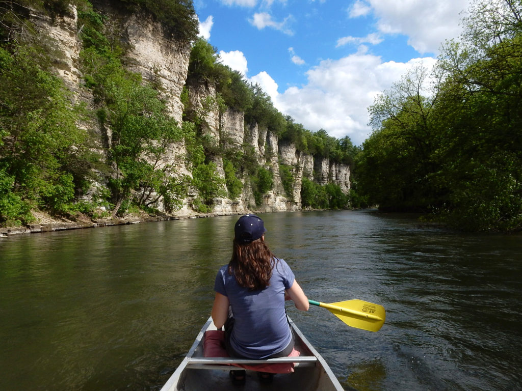 A person paddles a canoe down a river running through a canyon.