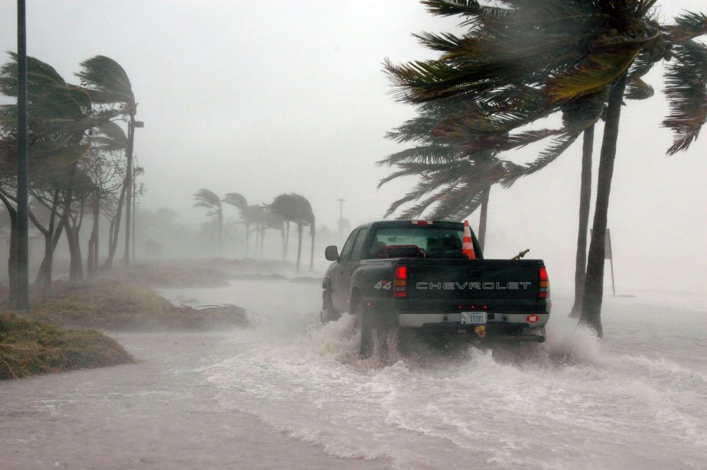 Pickup truck on flooded beach road during hurricane.