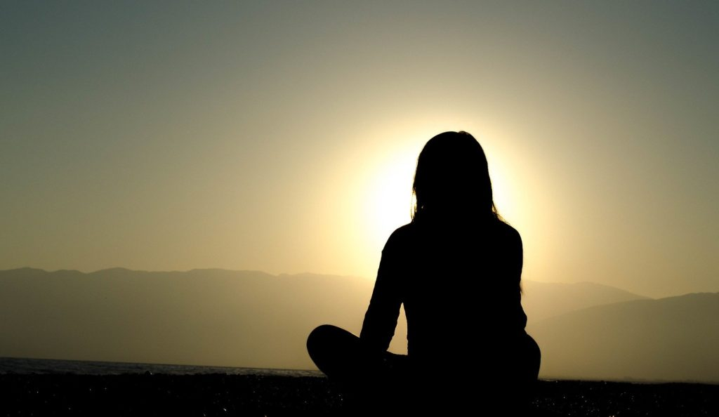 Silhouette of woman meditating on mountain.