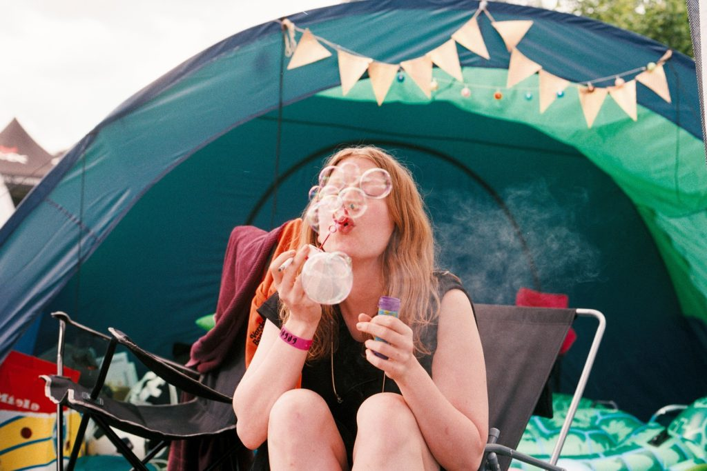 Woman camping by tent blows bubbles.