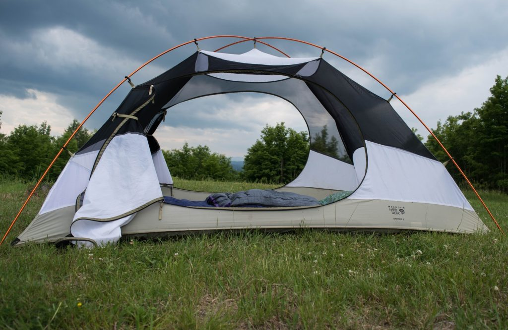 Large open camping tent in grassy meadow.